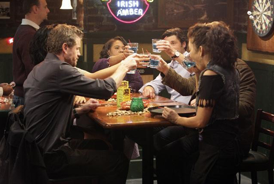 Grey's Anatomy characters drinking at bar.
