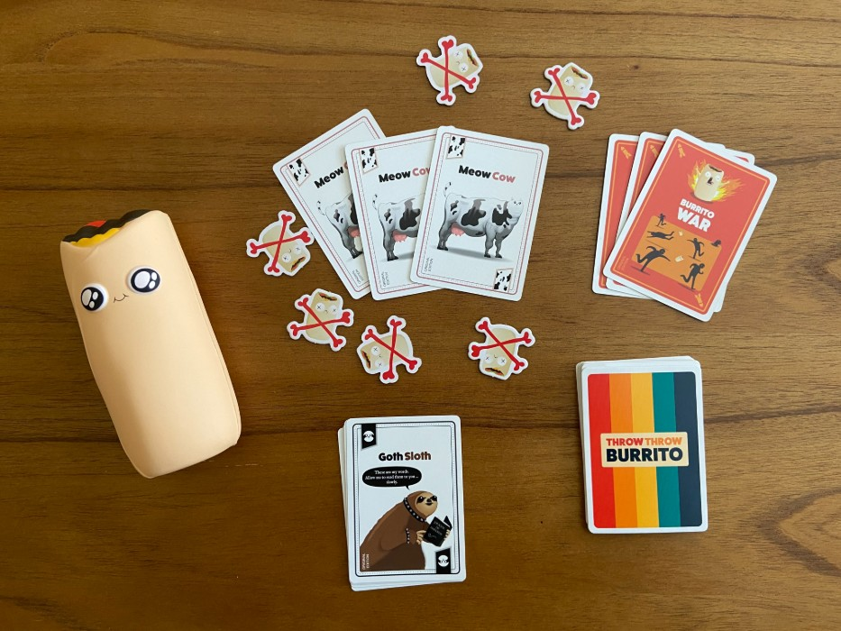 Throw throw burrito game pieces including cards and toy burrito.