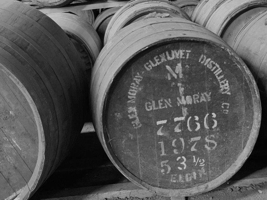 Black and white photo of a barrel at a distillery.