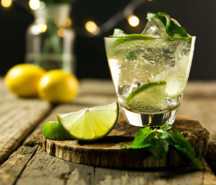 A mojito cocktail with lime slices.