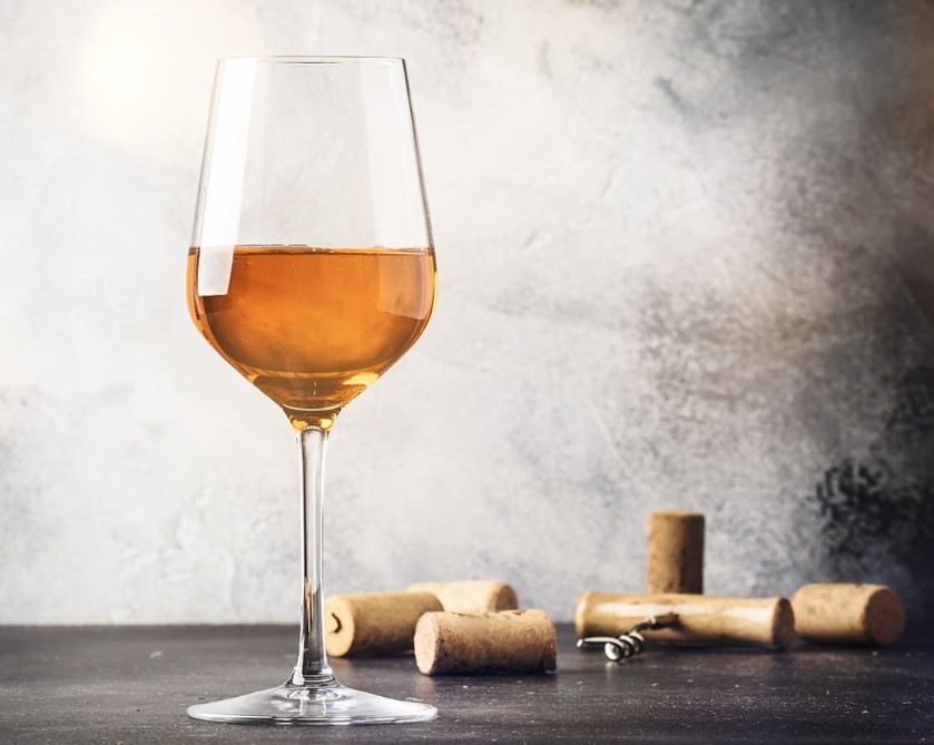 Orange wine in a glass next to corks.