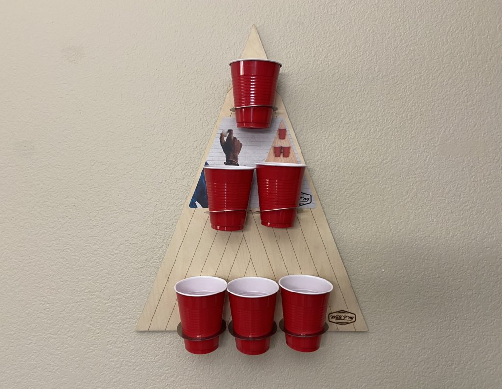 Free Pong board mounted to wall with red solo cups attached.
