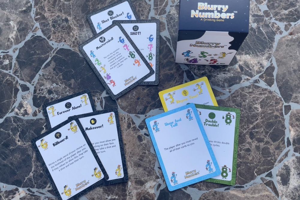 Blurry Number drinking game cards face up showing drinking challenges.